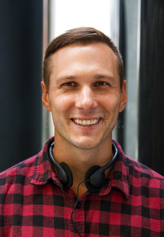 Portret van jonge mensenstudent bij station met hoofdtelefoons het glimlachen royalty-vrije stock fotografie