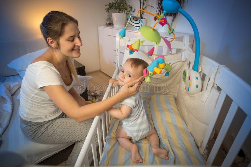 Portret van jonge moeder die haar baby in voederbak vóór goin bekijken stock afbeeldingen