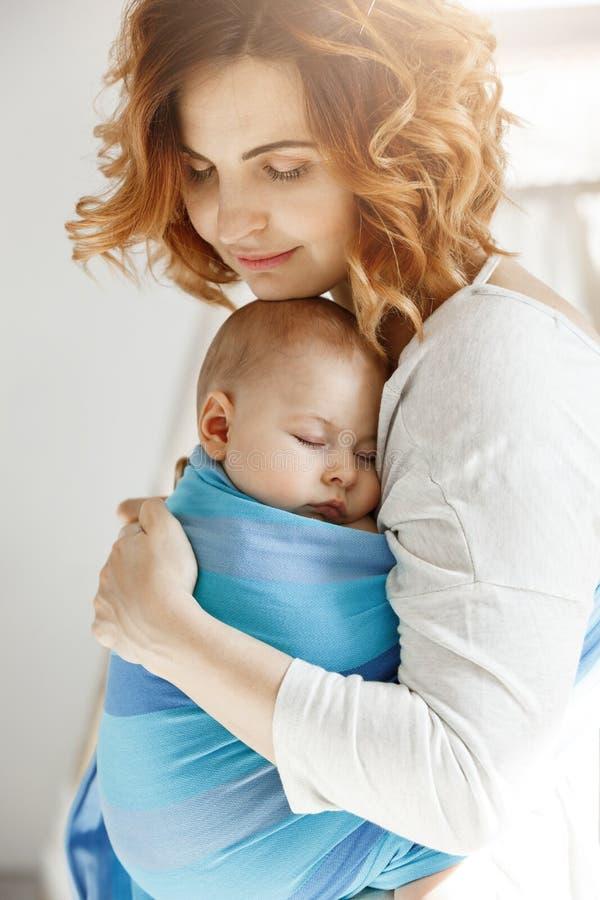 Portret van jonge moeder en pasgeboren zoonsslaap op moederborst in blauwe babyslinger Familiegeluk vibes Familie royalty-vrije stock foto