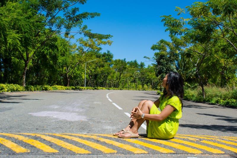 Portret van jonge mooie Aziatische meisjeszitting op de weg die kant bekijken stock foto's