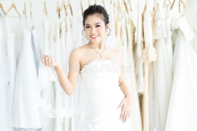 Portret van jonge mooie Aziatische vrouw status in kleedkamer van moderne huwelijkssalon en het bekijken camera De dag van het hu stock foto's
