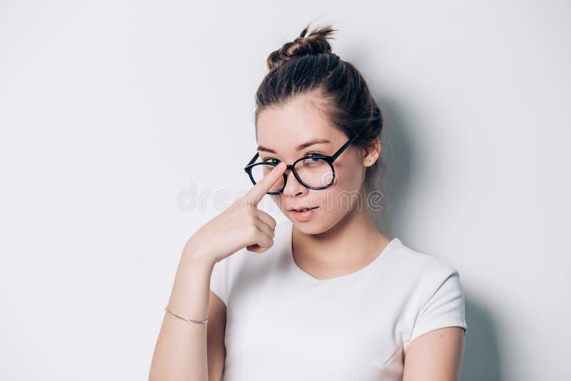 Portret van jonge mooie donkerbruine vrouw met glazen op witte achtergrond stock foto