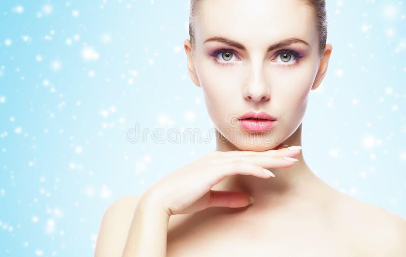 Portret van jonge, mooie en gezonde vrouw: over de winterachtergrond Gezondheidszorg, kuuroord, make-up en gezichts het opheffen  stock afbeeldingen