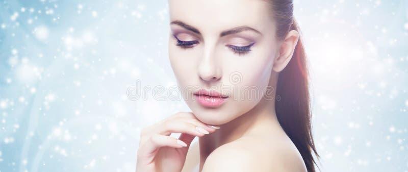 Portret van jonge, mooie en gezonde vrouw: over de winterachtergrond Gezondheidszorg, kuuroord, make-up en gezichts het opheffen  stock afbeelding