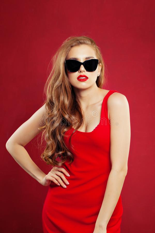 Portret van jonge mooie maniervrouw die rode kleding en zwarte zonnebril dragen modelmeisje met rode lippenmake-up op rood royalty-vrije stock foto