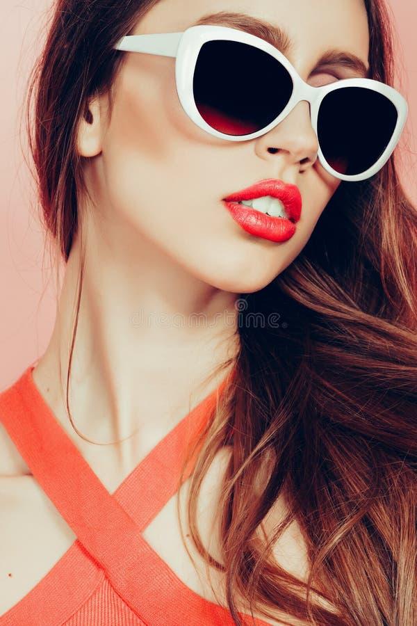 Portret van jonge mooie slanke vrouw in sexy kleding met sensuele lippen in studio die zonnebril dragen het glimlachen en het ste royalty-vrije stock afbeeldingen