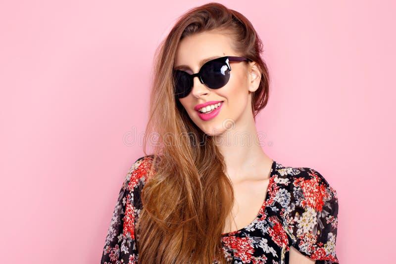 Portret van jonge mooie slanke vrouw in sexy kleding met sensuele lippen in studio die zonnebril dragen het glimlachen en het ste royalty-vrije stock afbeelding