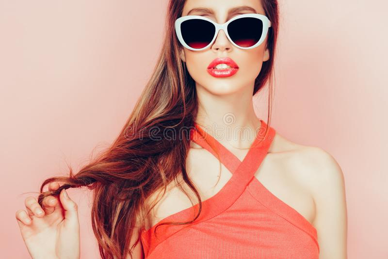 Portret van jonge mooie slanke vrouw in sexy kleding met sensuele lippen in studio die zonnebril dragen het glimlachen en het ste stock afbeeldingen