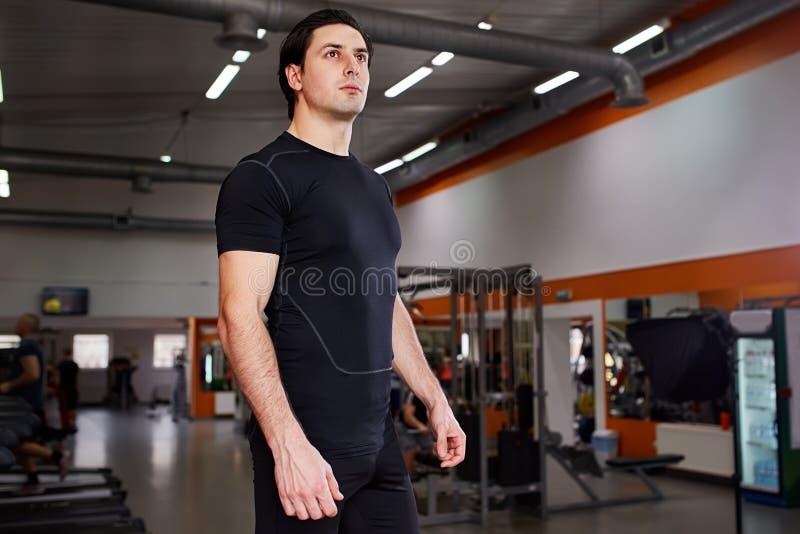 Portret van jonge mooie sportman in zwarte sportwear terwijl status met in gymnastiek royalty-vrije stock foto's