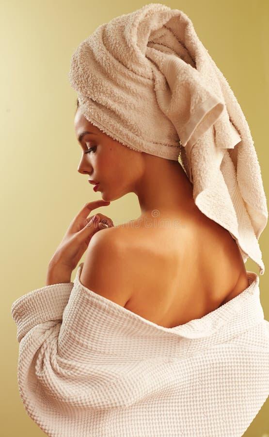 Portret van jonge mooie vrouw die badjas en handdoek op haar hoofd in slaapkamer dragen royalty-vrije stock fotografie
