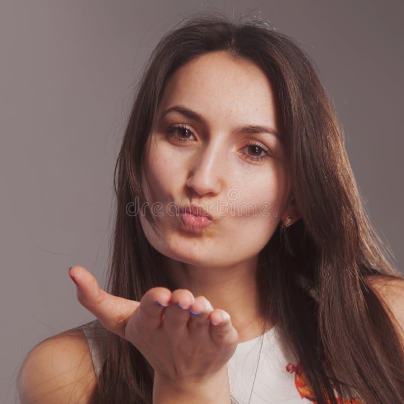 Portret van jonge mooie vrouw die luchtkus verzenden als symbool van liefde royalty-vrije stock afbeelding