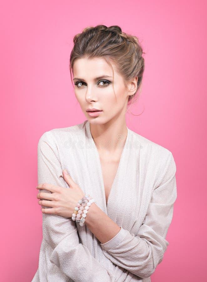 Portret van jonge mooie vrouw in een lichtgrijze blouse Armband of parels op hand stock foto
