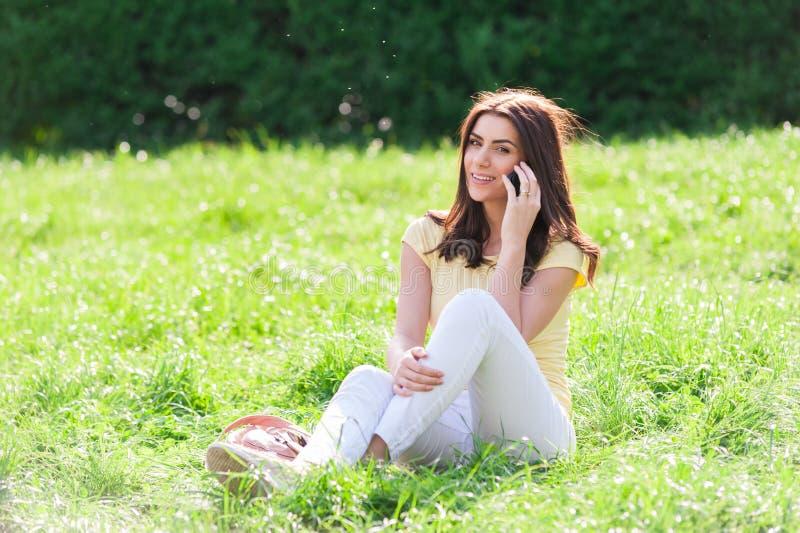 Portret van jonge mooie vrouw in het park die van de de zomerstad op een celtelefoon spreken stock foto's