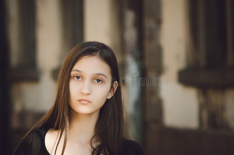 Portret van jonge mooie mooie vrouw met het lange haar stellen in stad stock afbeelding