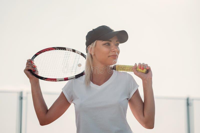 Portret van jonge mooie vrouw met racket voor tennis op een hof royalty-vrije stock afbeeldingen