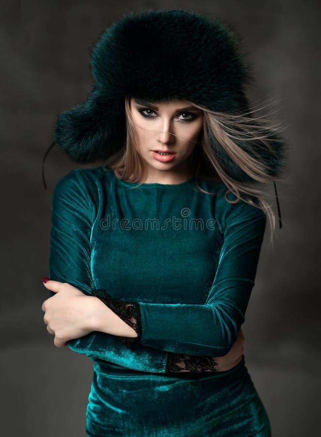Portret van jonge mooie vrouw in nieuwe groene van het de winterbont van de manier poolvos het oorkleppen royalty-vrije stock afbeelding