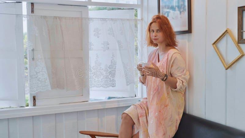 Portret van jonge mooie vrouw status naast venster en het drinken koffie royalty-vrije stock foto's