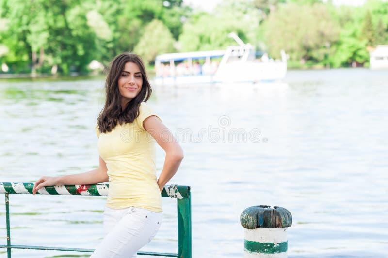 Portret van jonge mooie vrouw tegen meer in het park van de de zomerstad stock afbeeldingen