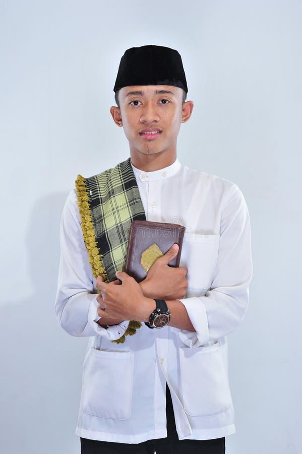 Portret van jonge moslim die heilige Quran dragen bij ramadan kareem stock afbeeldingen