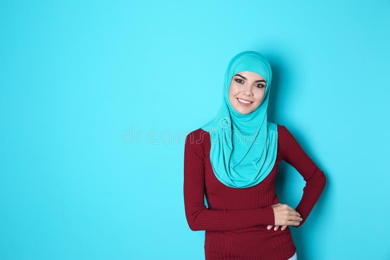 Portret van jonge Moslimvrouw in hijab tegen kleurenachtergrond stock afbeeldingen
