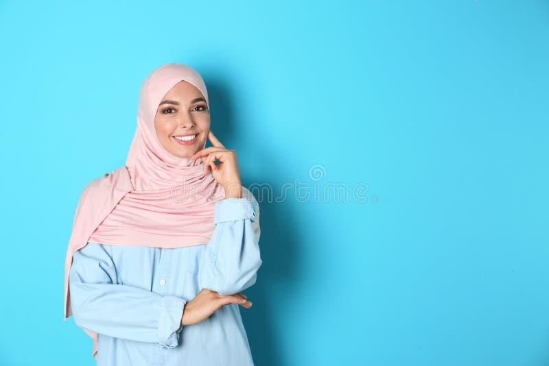 Portret van jonge Moslimvrouw in hijab tegen kleurenachtergrond royalty-vrije stock foto's