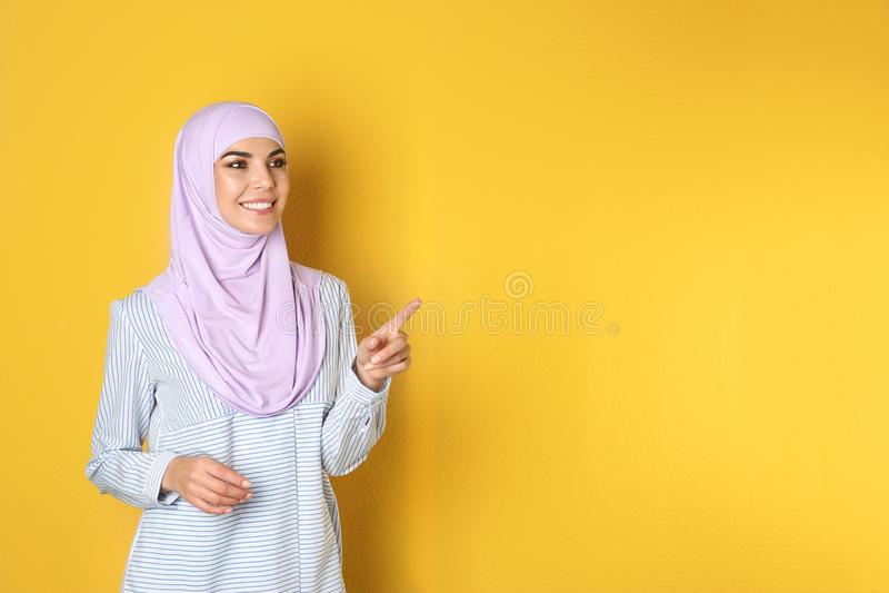 Portret van jonge Moslimvrouw in hijab tegen kleurenachtergrond royalty-vrije stock afbeeldingen