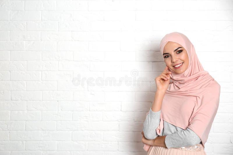 Portret van jonge Moslimvrouw in hijab tegen muur Ruimte voor tekst royalty-vrije stock afbeeldingen