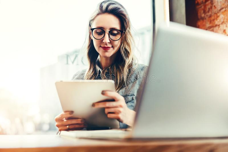 Portret van jonge onderneemster die in in glazen, in koffie voor laptop zitten, die tabletcomputer, het werken met behulp van stock foto