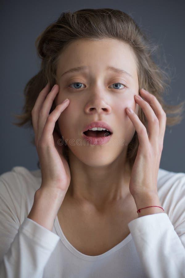 Portret van jonge opgeschrokken dame die droevig in camera terwijl het houden van haar handen dichtbij gezicht kijken stock afbeelding