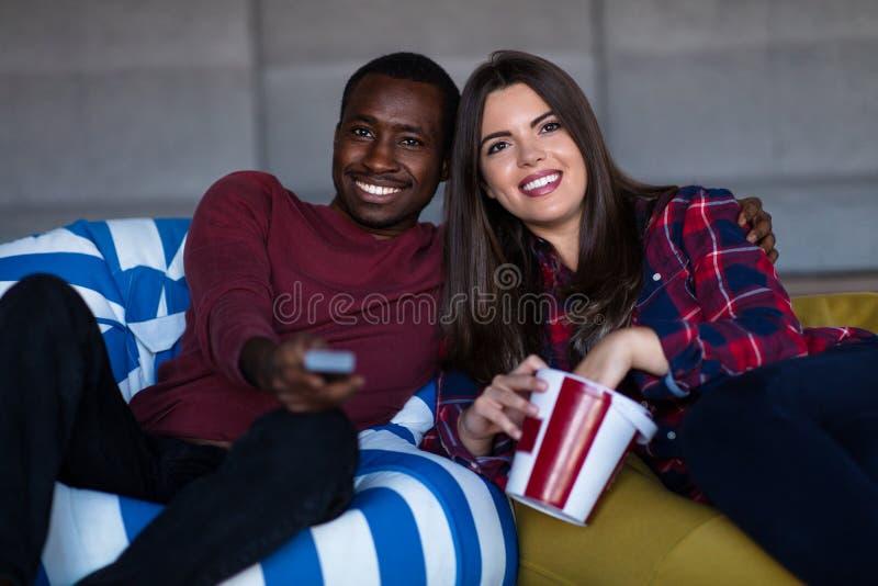 Portret van jonge paarzitting op bank die op een film met uitdrukking op hun gezichten letten royalty-vrije stock afbeelding