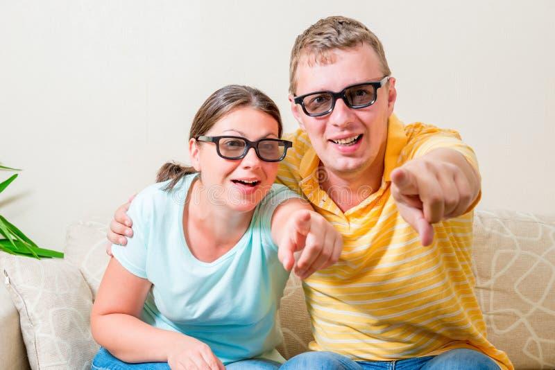 Portret van jonge paren die TV in 3D glazen kijken stock foto's