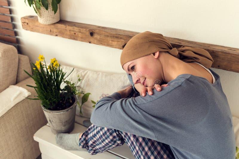 Portret van jonge positieve volwassen vrouwelijke kanker geduldige zitting in woonkamer in haar pyjama's royalty-vrije stock foto