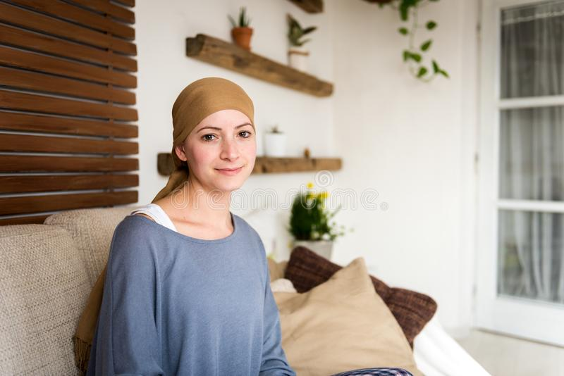 Portret van jonge positieve volwassen vrouwelijke kanker geduldige zitting in woonkamer, het glimlachen royalty-vrije stock fotografie