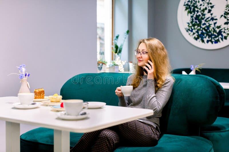 Portret van jonge, prachtige, vrouwelijke drinkthee en glimlachend uit het koffiewinkelvenster kijken terwijl ze geniet van haar royalty-vrije stock afbeeldingen