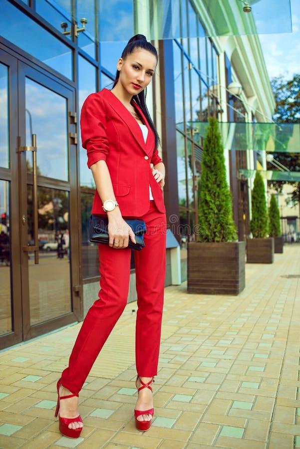 Portret van jonge schitterende dame met hoge poneystaart in rood kostuum en high-heeled schoenen die zich voor weerspiegeld winke stock fotografie