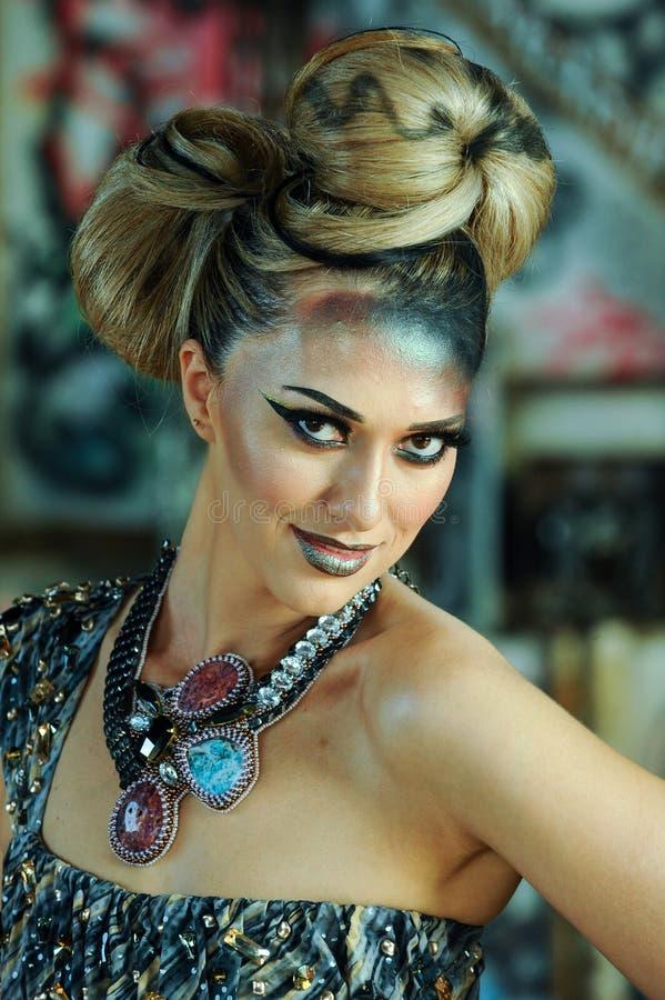 Portret van jonge schitterende glimlachende vrouw met creatief glamoursamenstelling en kapsel stock afbeeldingen