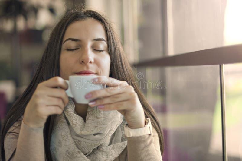 Portret van jonge schitterende vrouwelijke het drinken kop van koffie en het genieten van van haar alleen vrije tijd stock foto