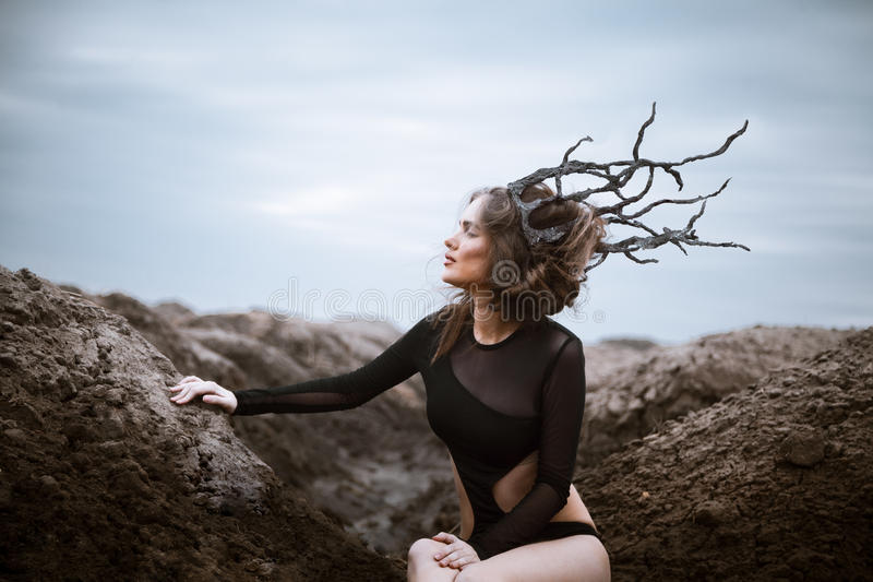 Portret van jonge schoonheidsvrouw met houten kroon Vreemd landschap royalty-vrije stock foto's