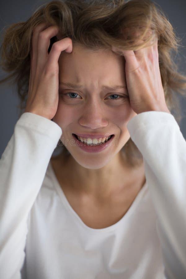 Portret van jonge schreeuwende dame die frustratedly in camera terwijl het houden van handen op haar hoofd kijken royalty-vrije stock fotografie