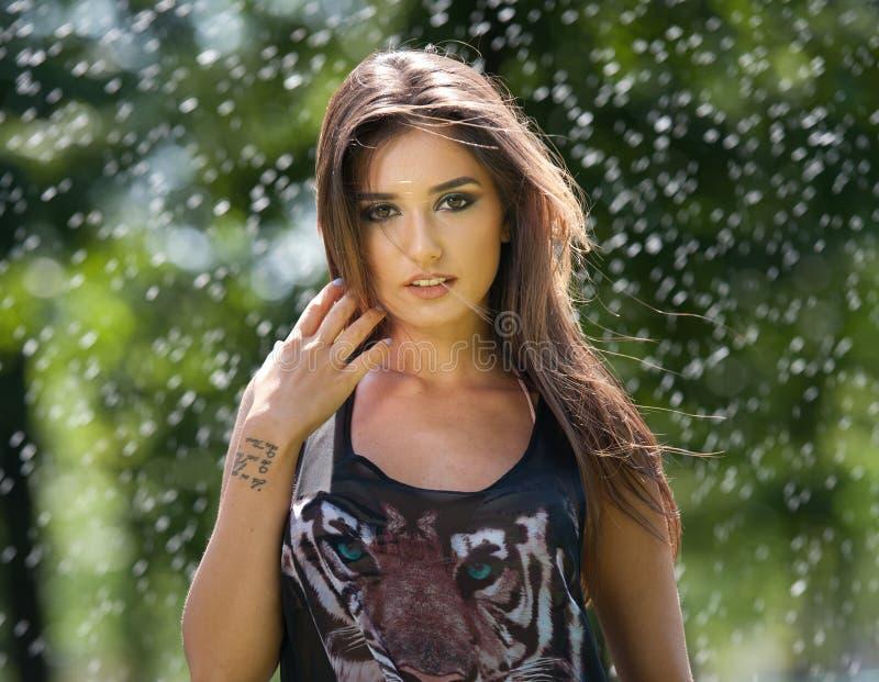Portret van jonge sexy vrouw in nevel van water Mooie meisjes met lange benen en glimlachen Gelukkige jonge vrouw in park Geluk,  stock fotografie