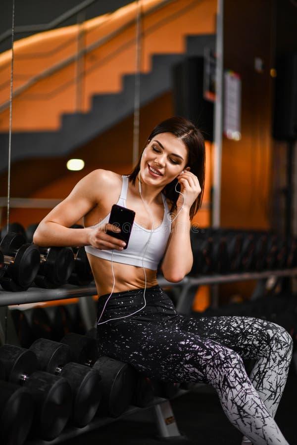 Portret van jonge sportvrouw met smartphone die aan muziek in gymnastiek luistert stock fotografie