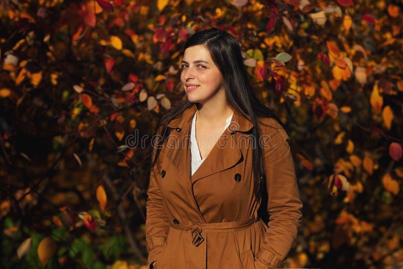Portret van jonge stedelijke stijlvrouw status bij park Het seizoen van de herfst Weg in dalingsbos royalty-vrije stock afbeelding