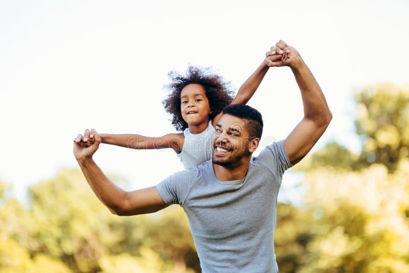 Portret van jonge vader die zijn dochter op zijn rug vervoeren