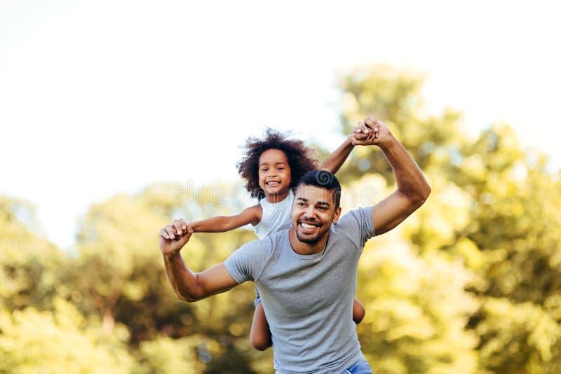 Portret van jonge vader die zijn dochter op zijn rug vervoeren royalty-vrije stock afbeeldingen