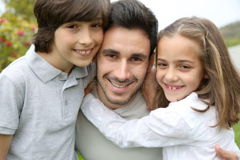 Portret van jonge vader met zijn kinderen stock foto's