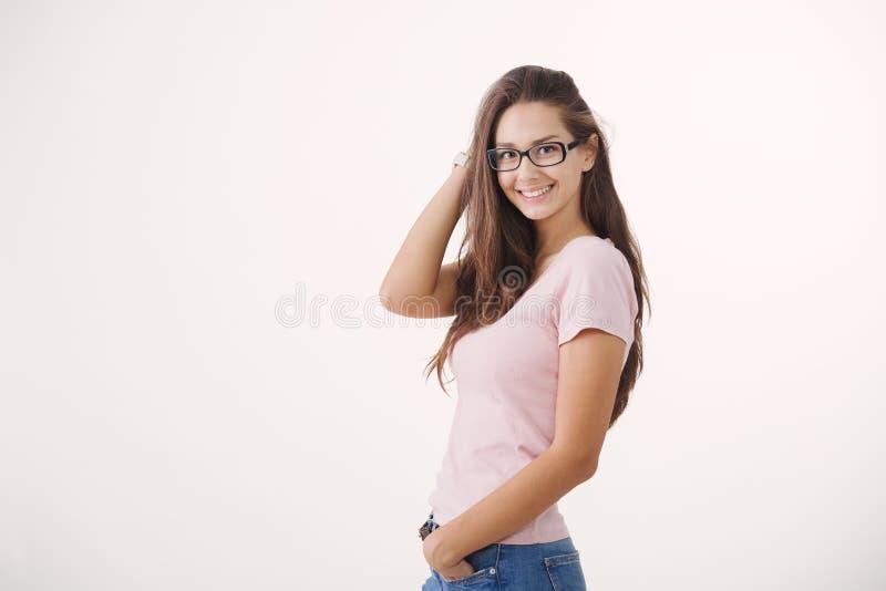 Portret van jonge vrolijke bruin-haired vrouw die glazen dragen tegen witte achtergrond royalty-vrije stock foto