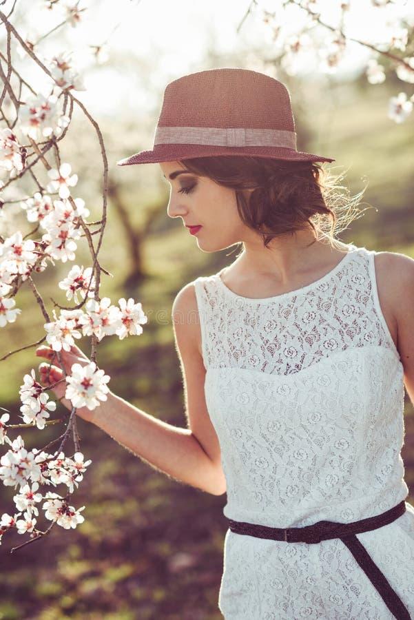Portret van jonge vrouw in de gebloeide tuin in de lente tim stock foto
