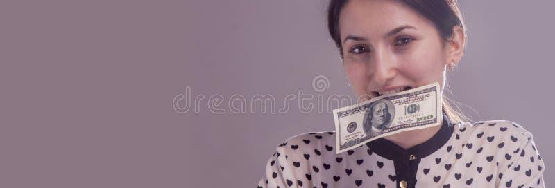 Portret van jonge vrouw die Amerikaanse dollargeld eten als symbool van omkoperij in politiek, zaken, diplomatie royalty-vrije stock foto