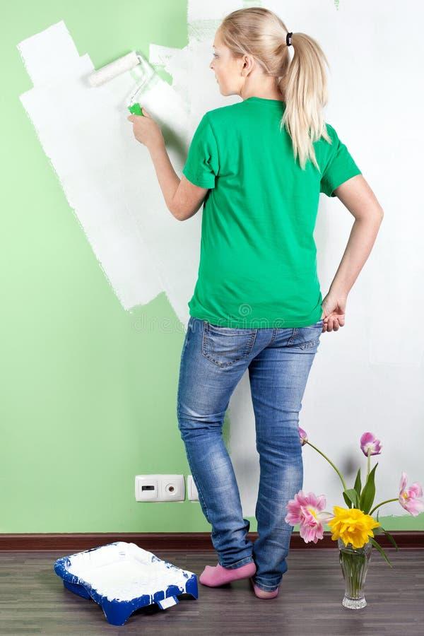 Portret van jonge vrouw die de muur schildert royalty-vrije stock afbeeldingen