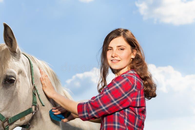 Portret van jonge vrouw die een mooi paard borstelen royalty-vrije stock foto